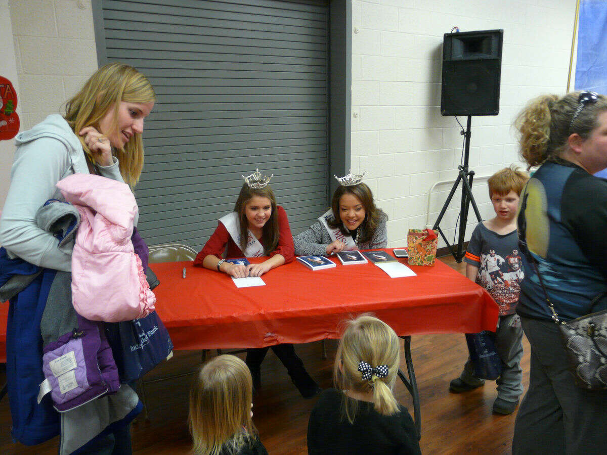 """Miss Auburn/Midland Outstanding Teen 2016Kendra Lodewyk, seated left, and Miss Auburn/Midland 2016Erin Jenkinson, make a special appearance at this year's Santa Fun Fest that took place on Tuesday at Williams Township Hall. The two pageant winners greeted children and provided them with autographed photographs of themselves at the """"Santa Stop."""""""