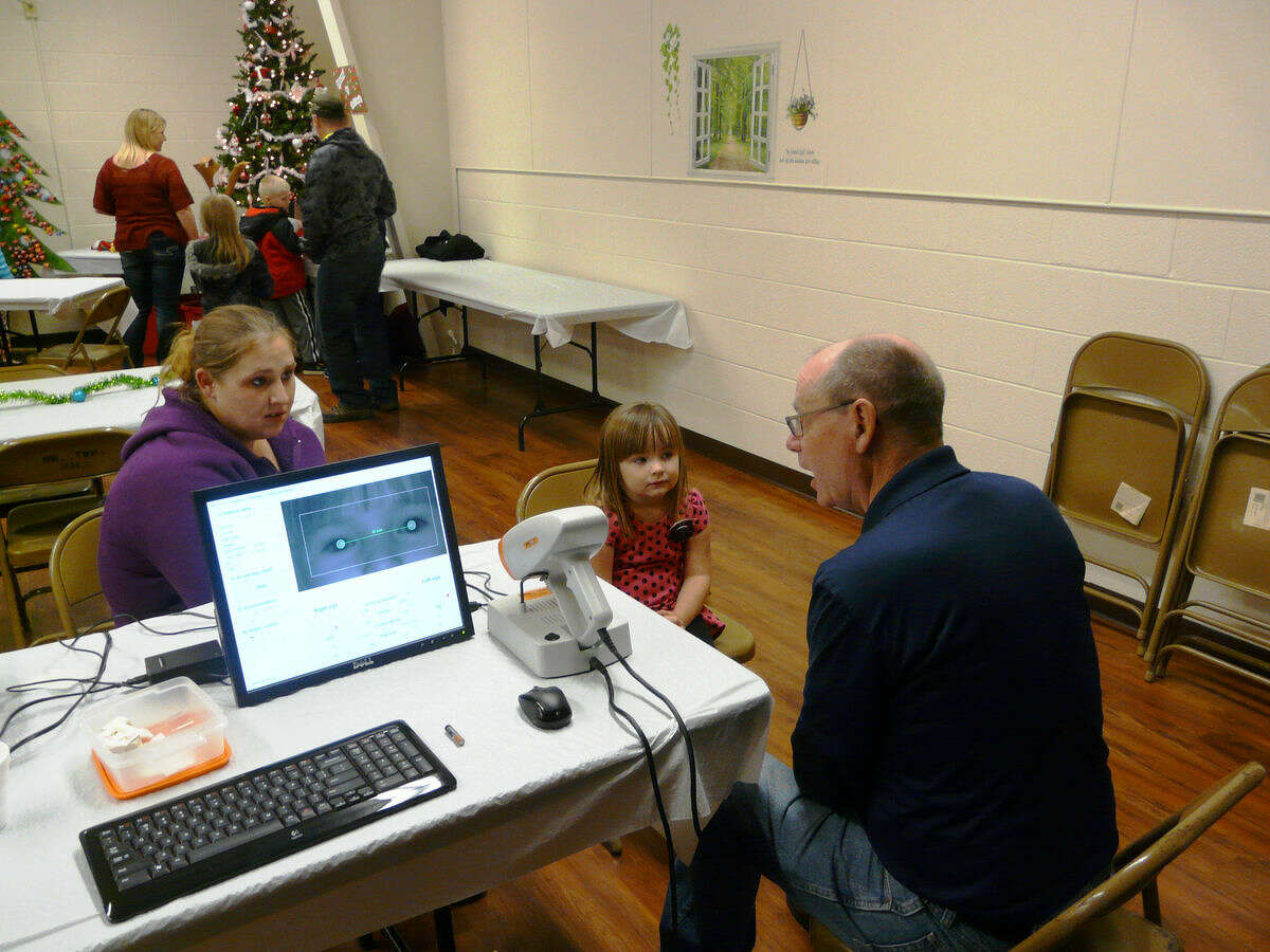 Lion Steve VanTol, right, administers a vision screening exam to Alaina Lincoln, 4, of Kawkawlin, at Auburn's Santa Fun Fest on Tuesday, while her mother, Shannon looks on.