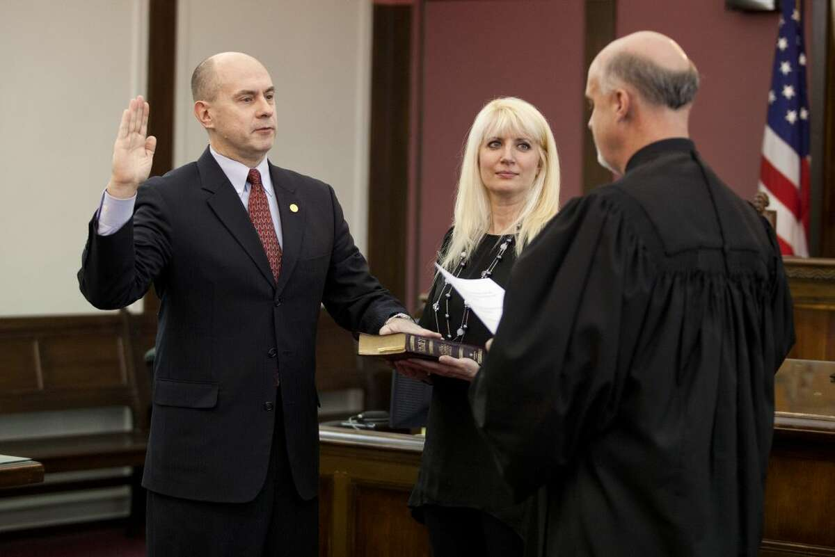 NEIL BLAKE   nblake@mdn.net Representative-elect Gary Glenn is sworn in by Judge Michael Carpenter as Gary's wife Annette holds the Bible during the ceremony at the Midland County Courthouse on Tuesday.