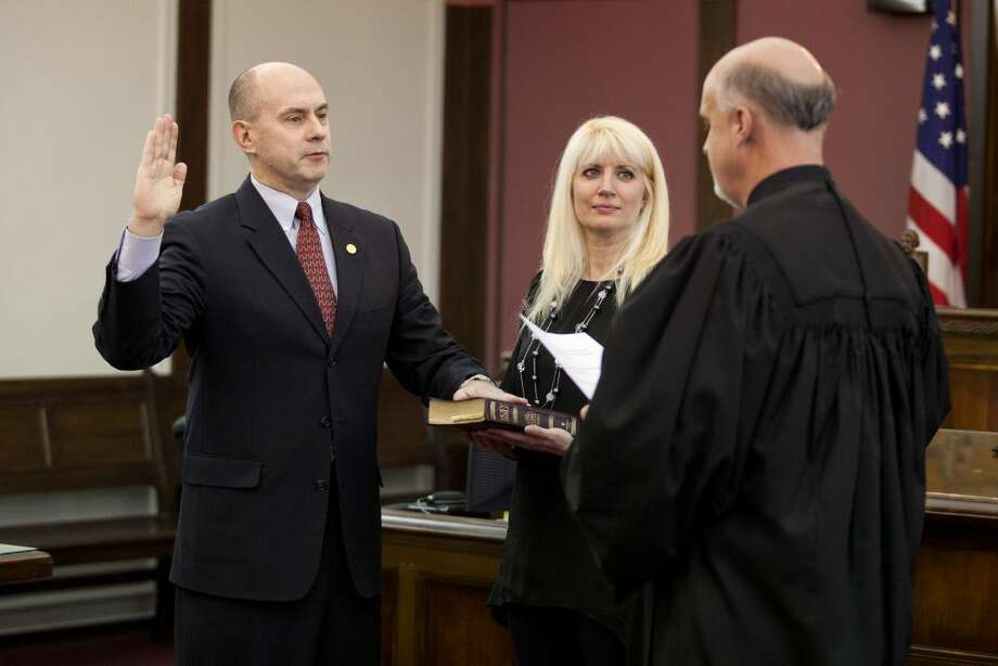 NEIL BLAKE | nblake@mdn.net Representative-elect Gary Glenn is sworn in by Judge Michael Carpenter as Gary's wife Annette holds the Bible during the ceremony at the Midland County Courthouse on Tuesday. Photo: Neil Blake/Midland Daily News