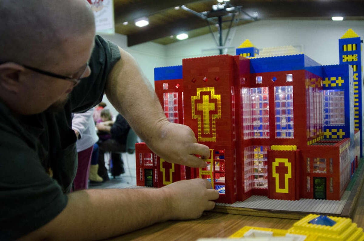 John Kraemer places windows on the Lego church that he built in Thomas Township. Kraemer designs and builds a church out of Legos and displays it at his church each year as a Christmas season tradition.