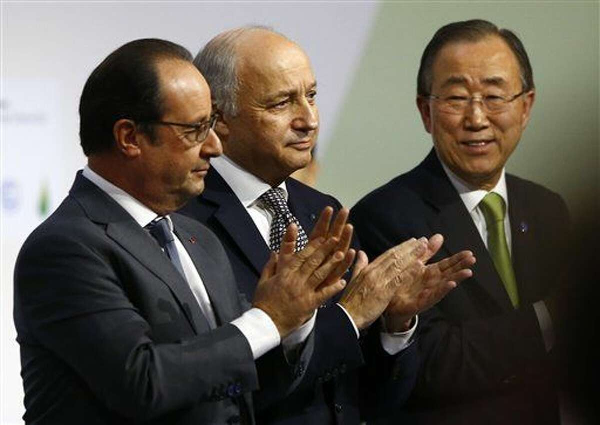 """French President Francois Hollande, left, French foreign minister Laurent Fabius, center, and United Nations Secretary General Ban Ki-moon applaud at the COP21, the United Nations Climate Change Conference, in Le Bourget, north of Paris, Saturday. Fabius says a """"final"""" draft of a global climate pact would be legally binding."""