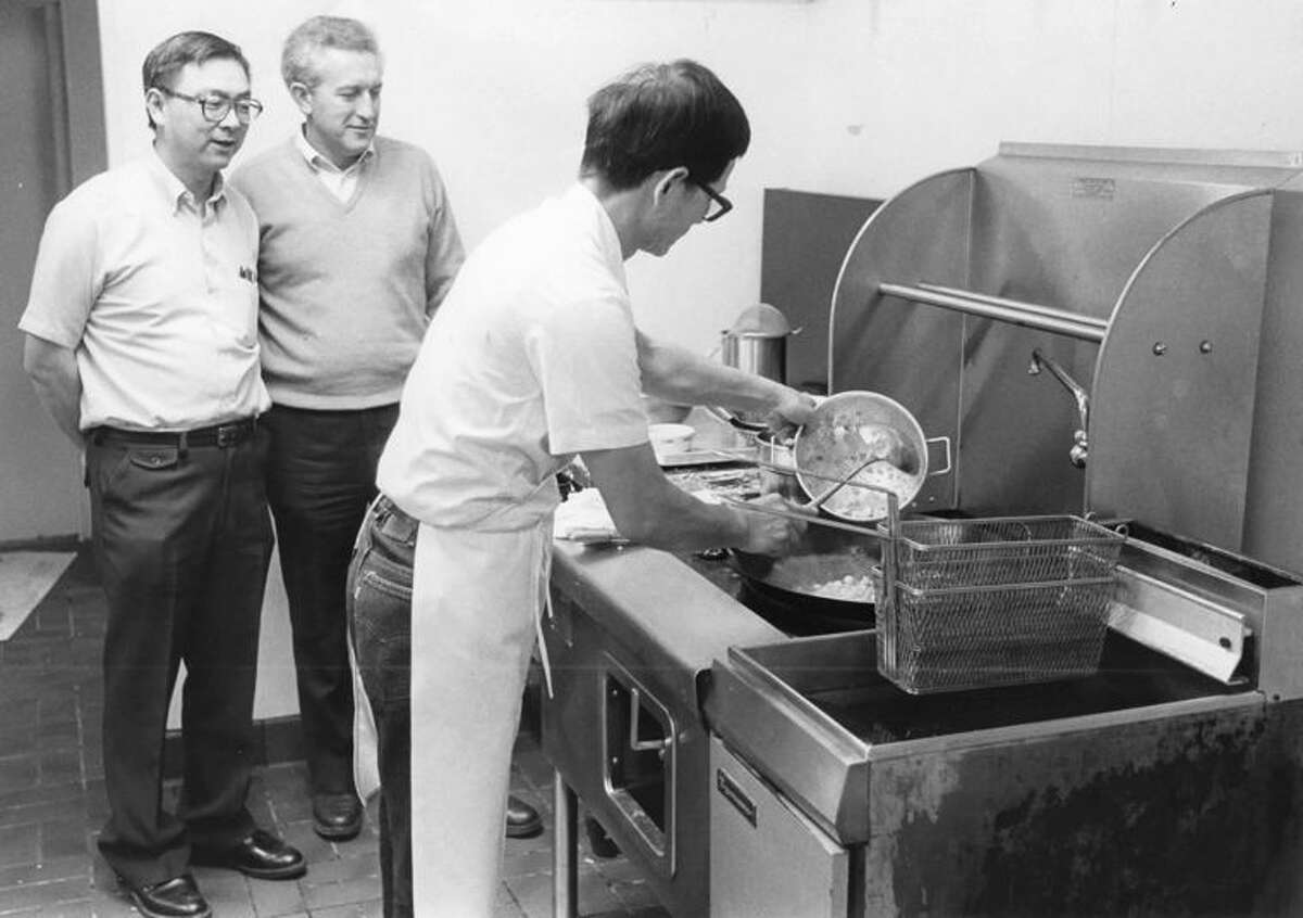 Carl Chow, left, and Larry Wegner watch Jack Hu prepare a wok full of almond chicken at their new Chinese fast-food restaurant.