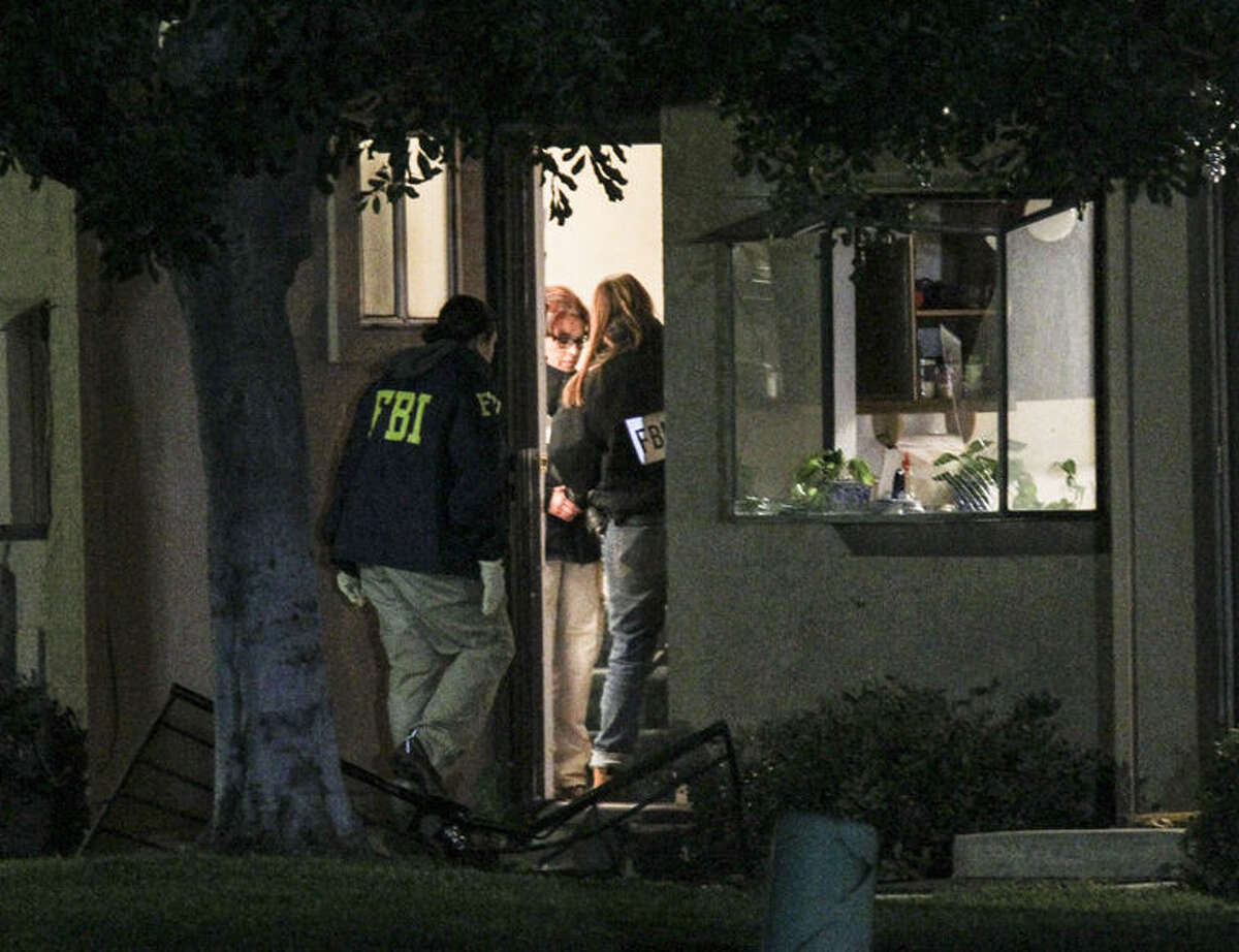 FBI agents search outside a home in connection to the shootings in San Bernardino, Thursday, Dec. 3, 2015, in Redlands, Calif.. A heavily armed man and woman opened fire Wednesday on a holiday banquet, killing multiple people and seriously wounding others in a precision assault, authorities said. Hours later, they died in a shootout with police. (AP Photo/Ringo H.W. Chiu)