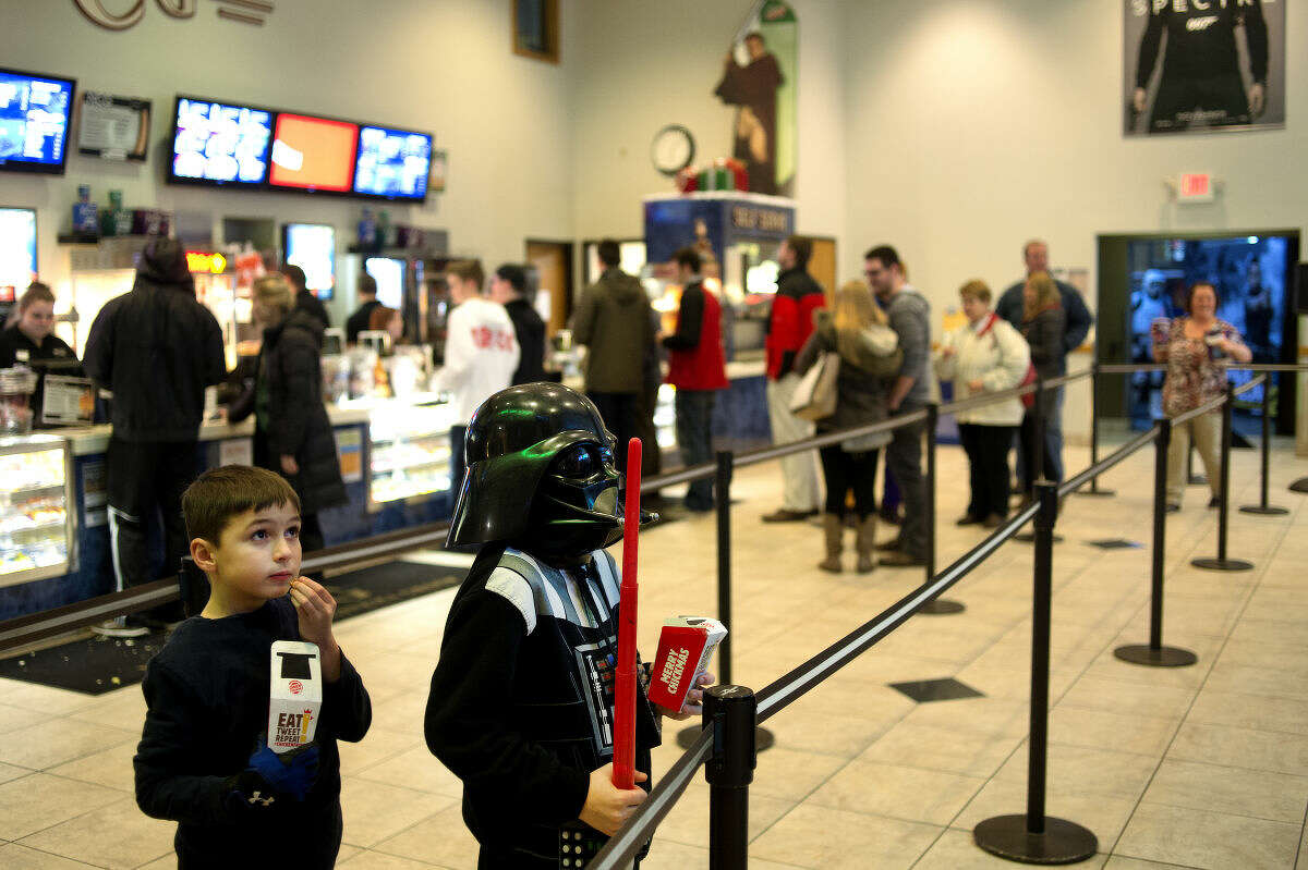 """Seven-year-old Christopher Applegate, left, and his brother 9-year-old Tyrus Applegate, both of Midland, watch movie previews while waiting in line for the 8 p.m. showing of """"Star Wars: The Force Awakens"""" at NCG Midland Cinemas Thursday evening. Tyrus dressed up like Darth Vader for the movie. """"I had the sweatshirt and my dad had the helmet,"""" Tyrus said. """"Luke Skywalker is my favorite but my brother wanted to be him so I decided to be Darth Vader."""" Tickets to the opening show at 7 p.m. and 8 p.m. both sold out."""