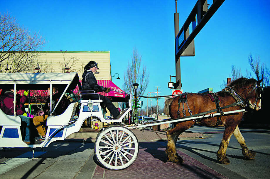 NICK KING | nking@mdn.net Kelly Townsend, of Town's End Clydesdales & Carriage, gives patrons a ride in a carriage pulled by Flash the clydesdale on Main Street. The free rides were part of Holly Jolly Days in Downtown Midland. Photo: Nick King/Midland Daily News