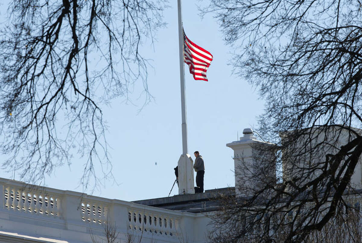 Workers lower the American flag above the White House in Washington, Thursday, Dec. 3, 2015. President Barack Obama ordered that flags be lowered at all government buildings to honor the victims of yesterday's mass shooting in San Bernardino, Calif. (AP Photo/Pablo Martinez Monsivais)