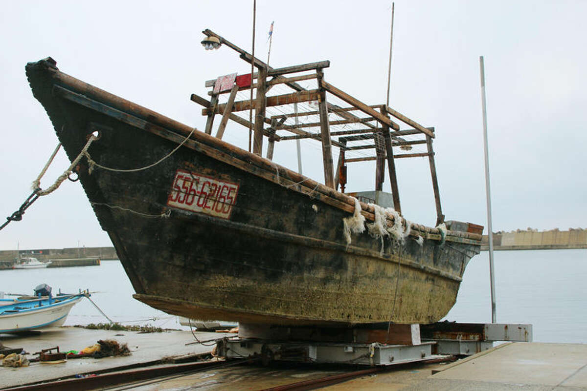 This Nov. 29, 2015 photo shows a ship of unknown nationality in Wajima, Ishikawa prefecture, central Japan, after it was found in mid-November off Noto peninsula and was towed to the shore. Japanese authorities are investigating nearly a dozen wooden boats carrying decomposing bodies found drifting off the northwestern coast over the past month. Coast Guard officials said Tuesday, Dec. 1, 2015, they have found at least 11 shoddy boats, carrying the bodies of unknown nationality since late October. They have also found fishing equipment and nets on board and signs written in Korean, suggesting they came from North Korea. (Kyodo News via AP) JAPAN OUT, CREDIT MANDATORY