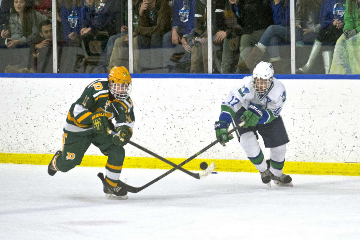 Dow's John Wilson and Saginaw Heritage's Brandon Martin battle for possession of the puck on Wednesday at Saginaw Bay Ice Arena.