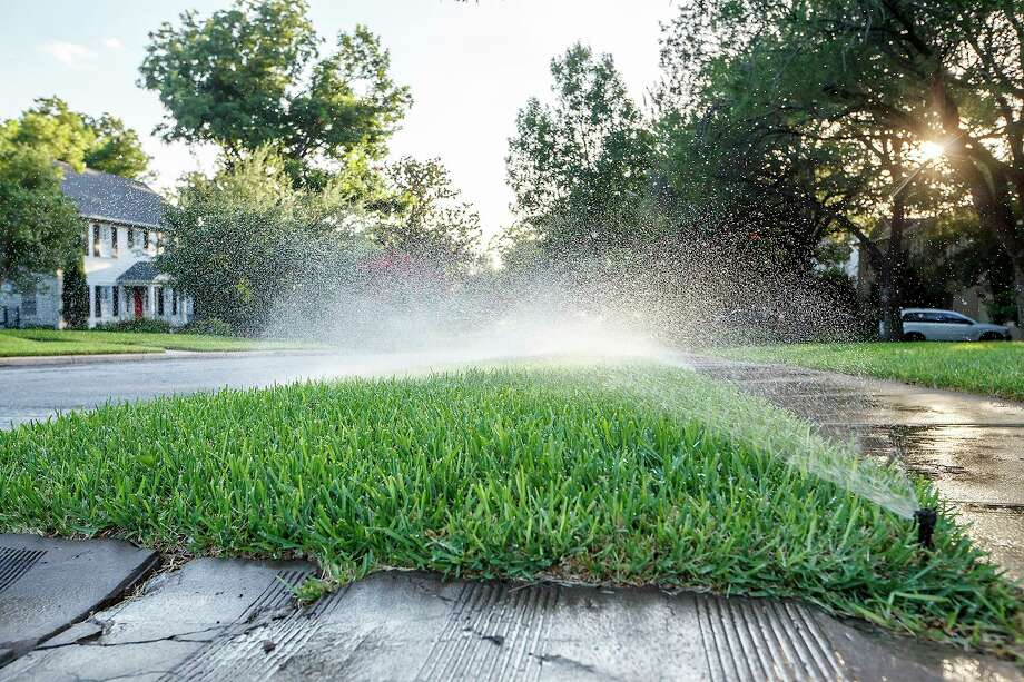 Sprinklers water a home in 2013. Now SAWS offers a pilot program that will allow users to change watering times remotely. That's the kind of conservation measures San Antonio needs. Photo: Express-News File Photo / Express-News 2013