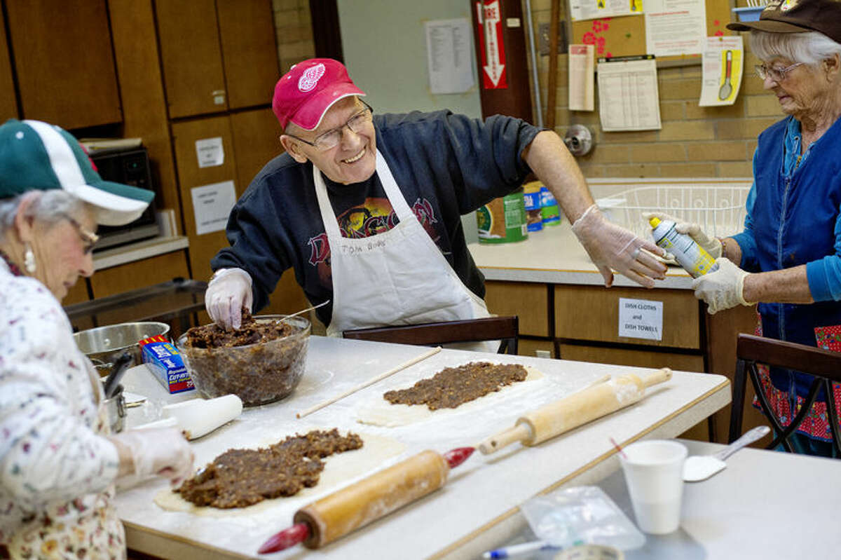Tom Boks, center, smiles as Clara Hancock, right, sprays oil on his hand to help lesson the stickiness as the two and Georgia Lang, left, work to make date pinwheels at Our Savior Lutheran Church in Midland. The group was preparing cookies to be sold at the church's annual Christmas Candy and Cookie Sale, set for Saturday, Dec. 12.