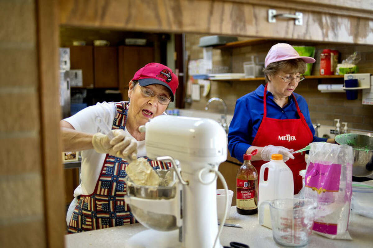 """Diana """"Dee"""" Zielinski, left, and Edie Carson make frosting at Our Savior Lutheran Church in Midland."""