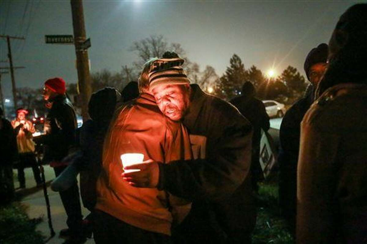 Clarence Strickland, father of Xavier Strickland, gets a hug during the candlelight vigil for Xavier Strickland on Saturday, Dec. 5, 2015, in Detroit. The 4-year-old Detroit boy who was mauled to death by pit bulls. Xavier Strickland and her son were walking to a school when the attack occurred. (Kimberly P. Mitchell/Detroit Free Press via AP)