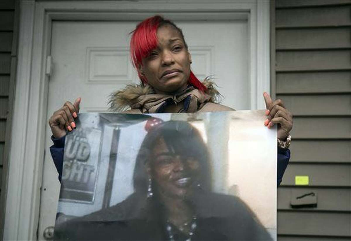 Latonya Jones, 19, holds a photo of her mother, Bettie Jones, during a vigil on Sunday, Dec. 27, 2015, in Chicago. Jones and Quintonio LeGrier, 19, were killed early Saturday by police responding to a domestic disturbance on the city's West Side, police said. (Ashlee Rezin/Chicago Sun-Times via AP) MANDATORY CREDIT, MAGS OUT, NO SALES; CHICAGO TRIBUNE OUT