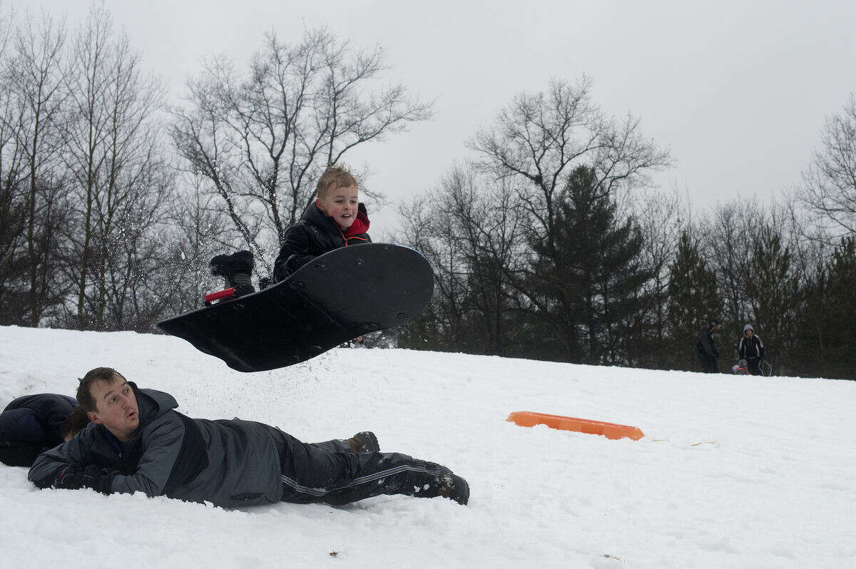 """Seven-year-old Sam Carn of Midland jumps over his father, Chuck Carn, while sledding down the hill at City Forest Tuesday afternoon. Chuck Carn packed snow together to make the jump for his sons and nieces. """"We came because it's the first real snow and my brother is visiting from Alabama,"""" Carn said. """"And they don't really get any snow."""""""