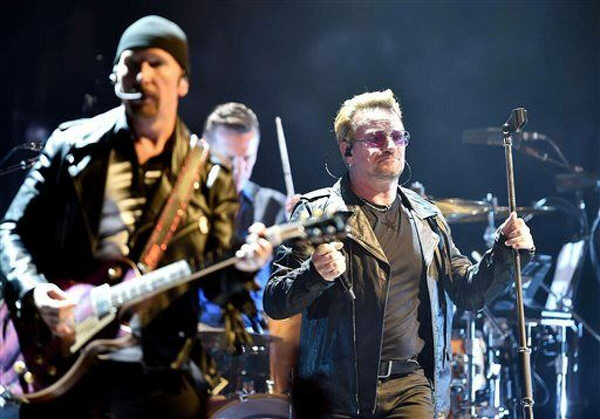 In this Sept. 4 file photo, Bono, right, leader of Irish rock band U2, performs in Turin, Italy. U2 has postponed its Saturday night concert in Paris in the light of the deadly attacks across the city Friday.