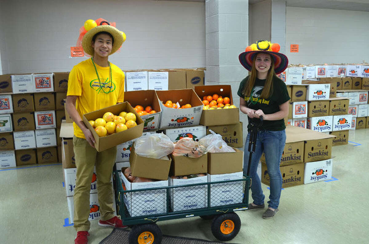 Andrew Wong and Brinli Leonhardt, the Dow High Charger Marching Band's senior drum majors, help distribute more than 2,000 cases of fresh premium citrus last February. The annual sale benefits Dow High's award winning music programs.