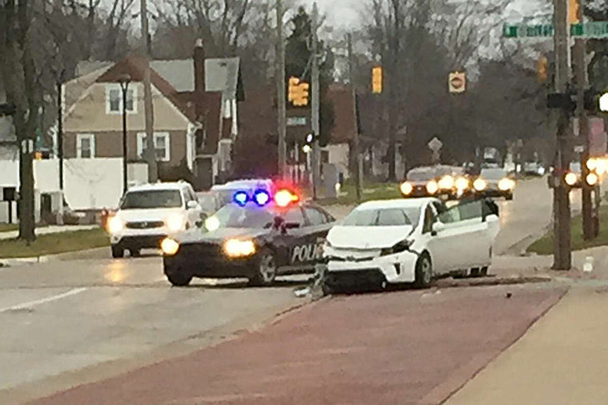 Midland Police work at the scene of this accident today at the intersection of Ashman and Buttles.