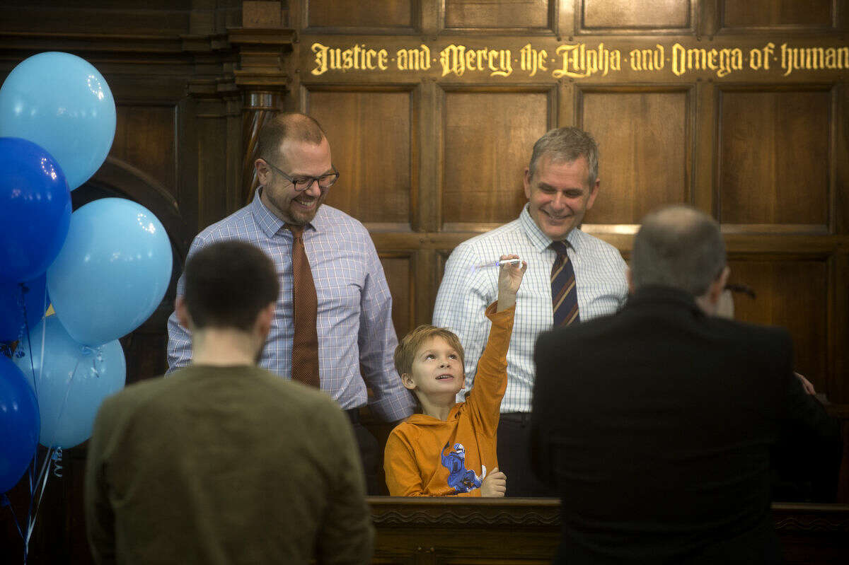 Steve Webb, left, and Matthew Mitchell watch as their newly adopted son, Eli Webb, 6, shows off his new pen, which Judge Dorene Allen used to finalized his step parent adoption Tuesday morning during Adoption Day at the Midland County Courthouse.