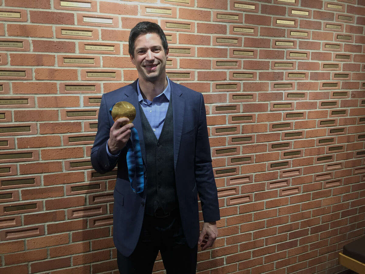 Steve Mesler poses Thursday night with his Olympic gold medal for bobsledding from the 2010 Olympics after speaking with members of the Leadership Midland Alumni Association at the Midland Center for the Arts.