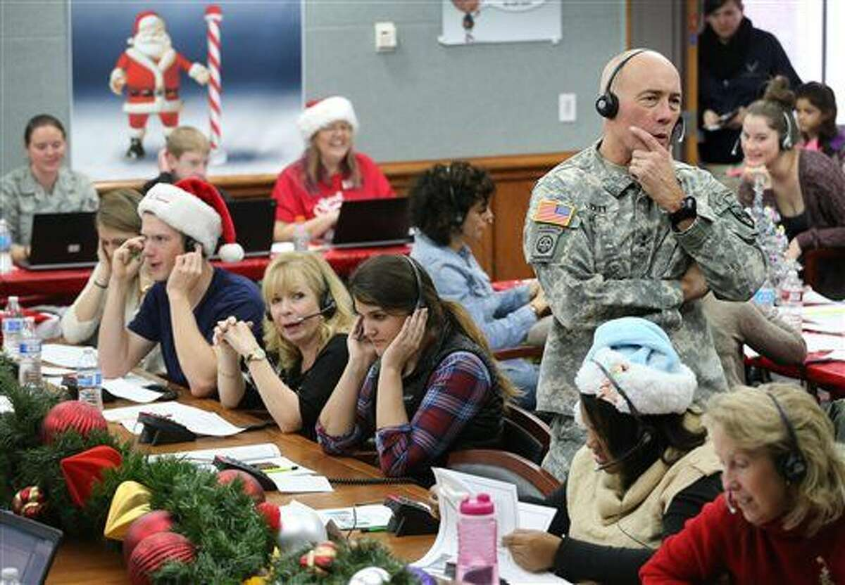 FILE - In this Dec. 24, 2014, file photo, NORAD and U.S. Northern Command (USNORTHCOM) Chief of Staff Maj. Gen. Charles D. Luckey joins other volunteers taking phone calls from children around the world asking where Santa is and when he will deliver presents to their homes, inside a phone-in center during the annual NORAD Tracks Santa Operation, at the North American Aerospace Defense Command, at Peterson Air Force Base, Colo. Hundreds of military and civilian volunteers at NORAD are estimated to field more than 100,000 calls this year through Christmas Eve, from children from all over the world eager to hear about Santa's progress. (AP Photo/Brennan Linsley, File)
