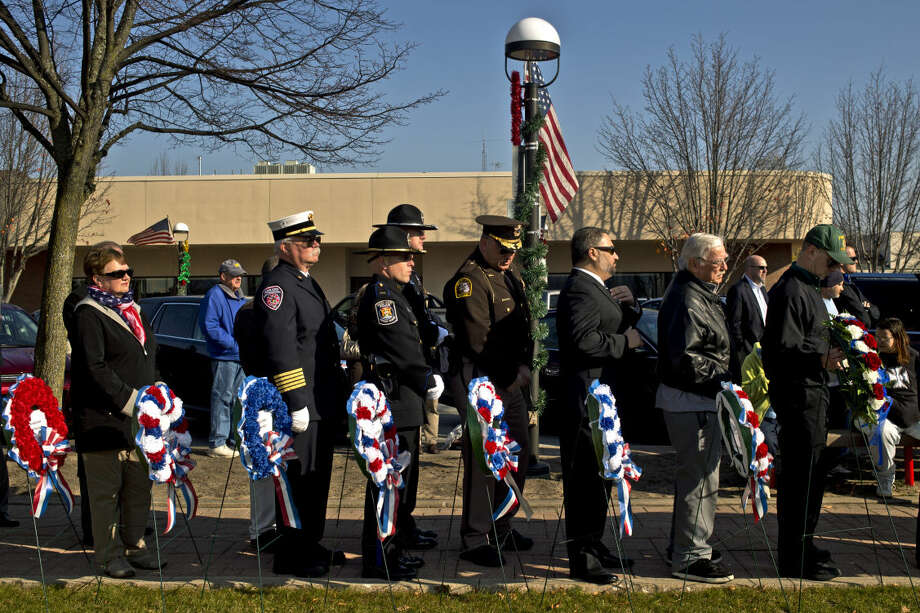 FILE — Participants line up with wreaths to decorate the Midland County Veterans Memorial outside the courthouse during a Veterans Day ceremony. Photo: Erin Kirkland | Midland Daily News
