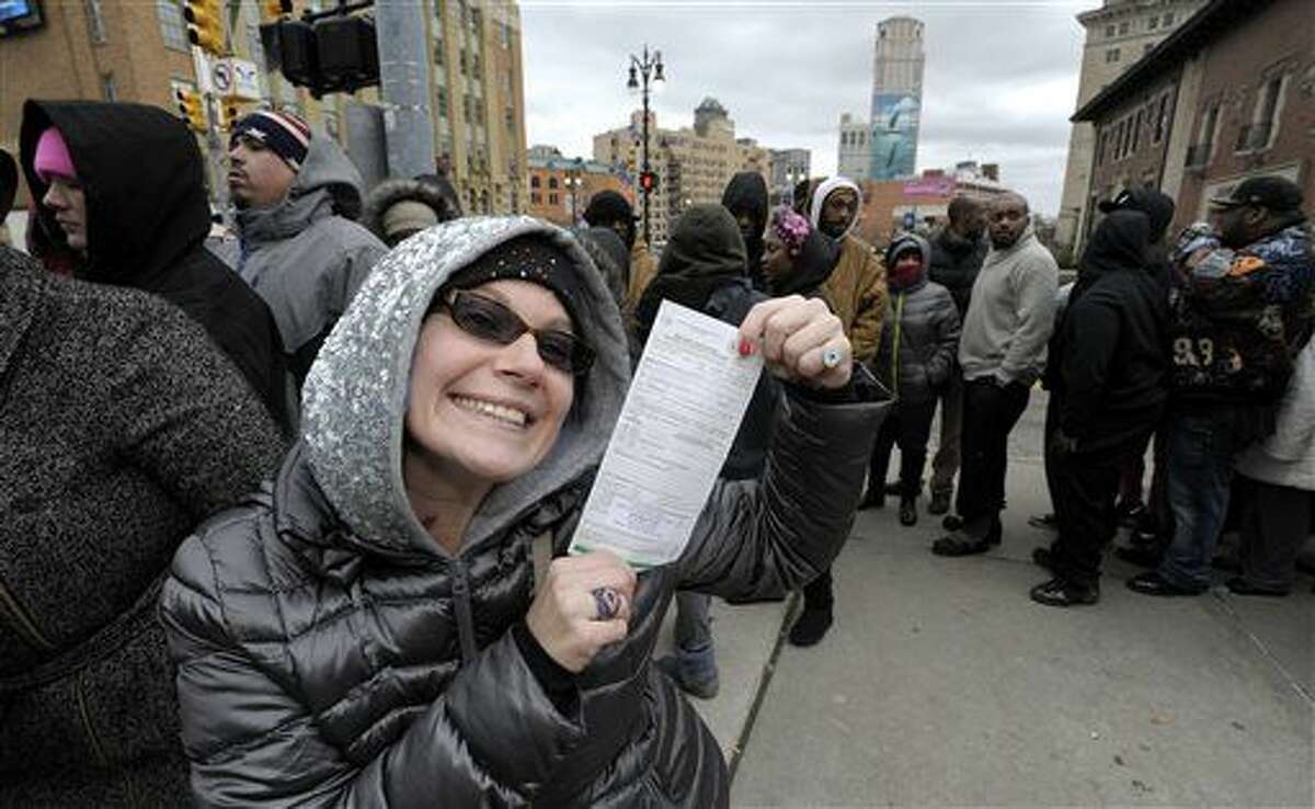 """Sabrina Gross, 38, of Garden City, shows off her $480 MI-DNR Uniform Law Citation for """"misconduct in a state park"""" as she waits in line, Wednesday. Throngs of people stand in line, Tuesday, Dec. 29, 2015, in Detroit as they wait to enter the courthouse during the 36th District Court 2-Day Holiday Sales Event where """"the court is waiving all late and warrant fees on outstanding balances owed on tickets."""" (Todd McInturf/The Detroit News via AP)"""