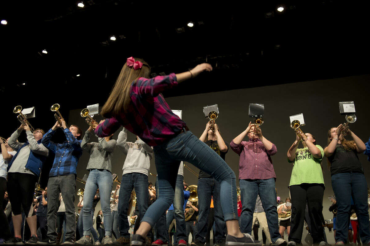 Midland High senior Katie Wenbanconducts the school's marching band in a song from the James Bond movies during the last rehearsal for Midland High's Rhapsody Rendezvous Thursday evening at the Midland Center for the Arts. The talent show will begin at 7:30 p.m. Friday evening at the Center for the Arts.