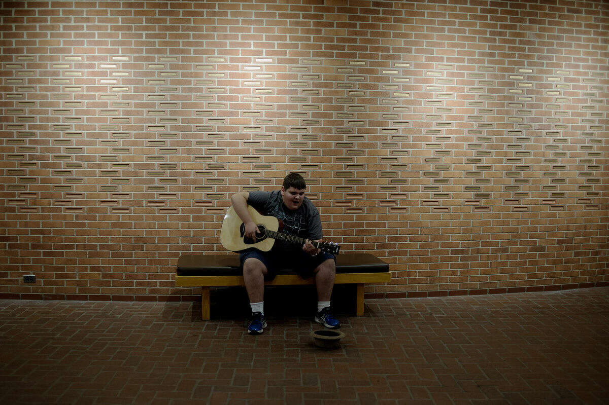 Midland High freshman Nathan Tata plays his guitar will waiting to rehearse with the school's choir during the last rehearsal for Midland High's Rhapsody Rendezvous Thursday evening at the Midland Center for the Arts. The talent show will begin at 7:30 p.m. Friday evening at the Center for the Arts.
