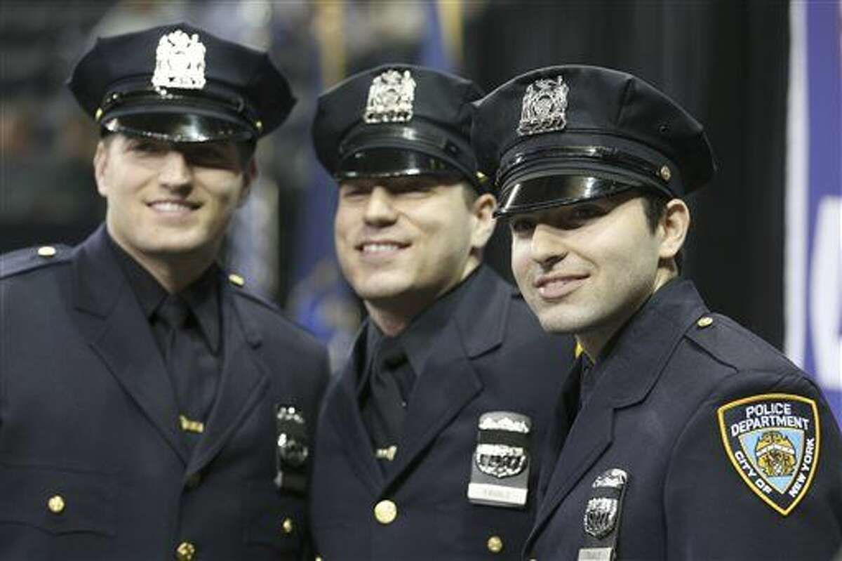 Brothers Stephan, left, John, center, and Alec Favale pose for photographers before the New York City Police Department Police Academy graduation ceremony, Tuesday, Dec. 29, 2015, at Madison Square Garden in New York. Three sons of a New York Police Department official were sworn in as officers Tuesday, in what may mark the first time three siblings have ever graduated from the city's police academy at one time.(AP Photo/Mary Altaffer)