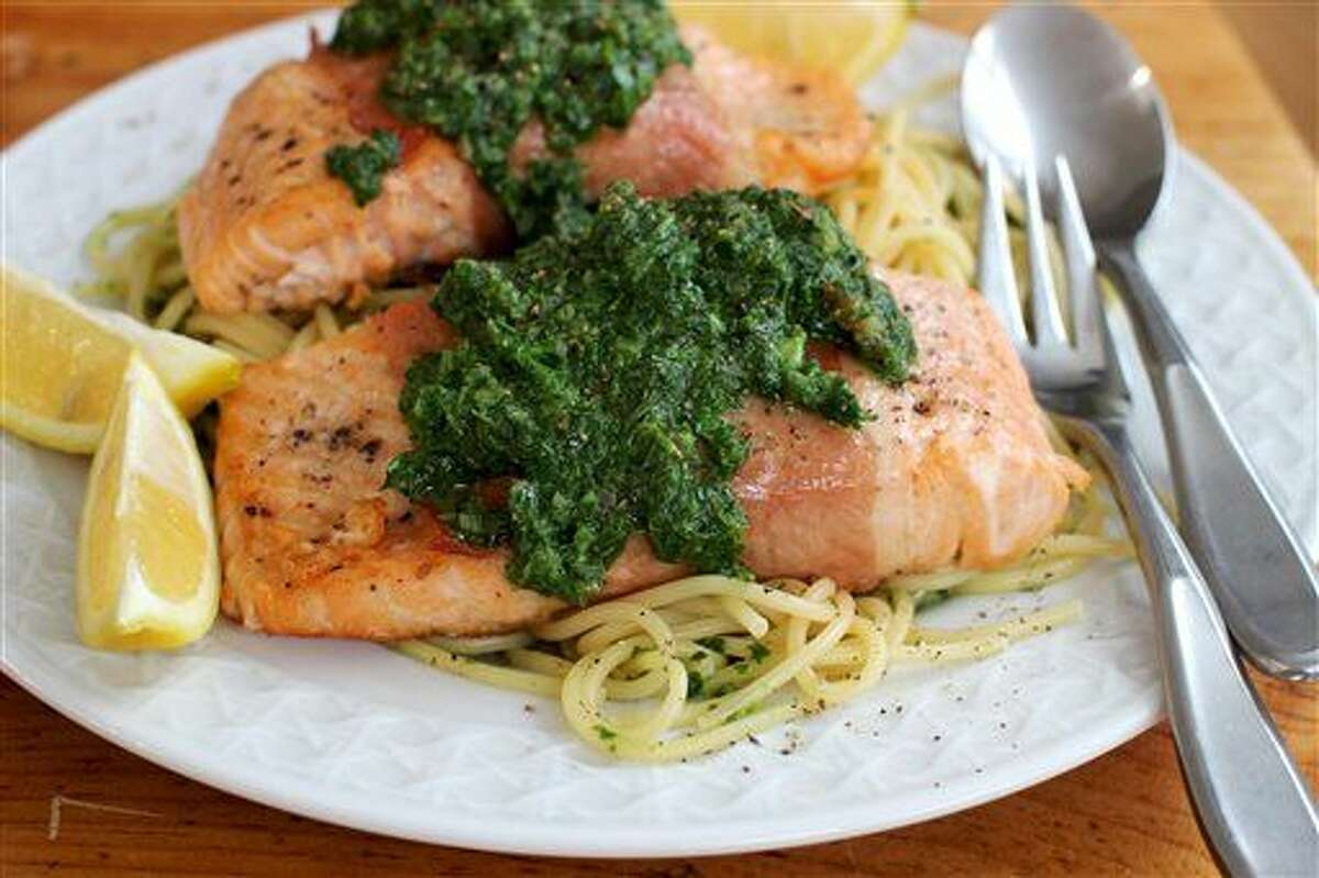 This Feb. 1, 2016 photo shows prosciutto wrapped salmon with fresh herb sauce in Concord, N.H. The key is to cook the puree in a skillet with a wide bottom, which allows it to heat up in a matter of minutes. (AP Photo/Matthew Mead)