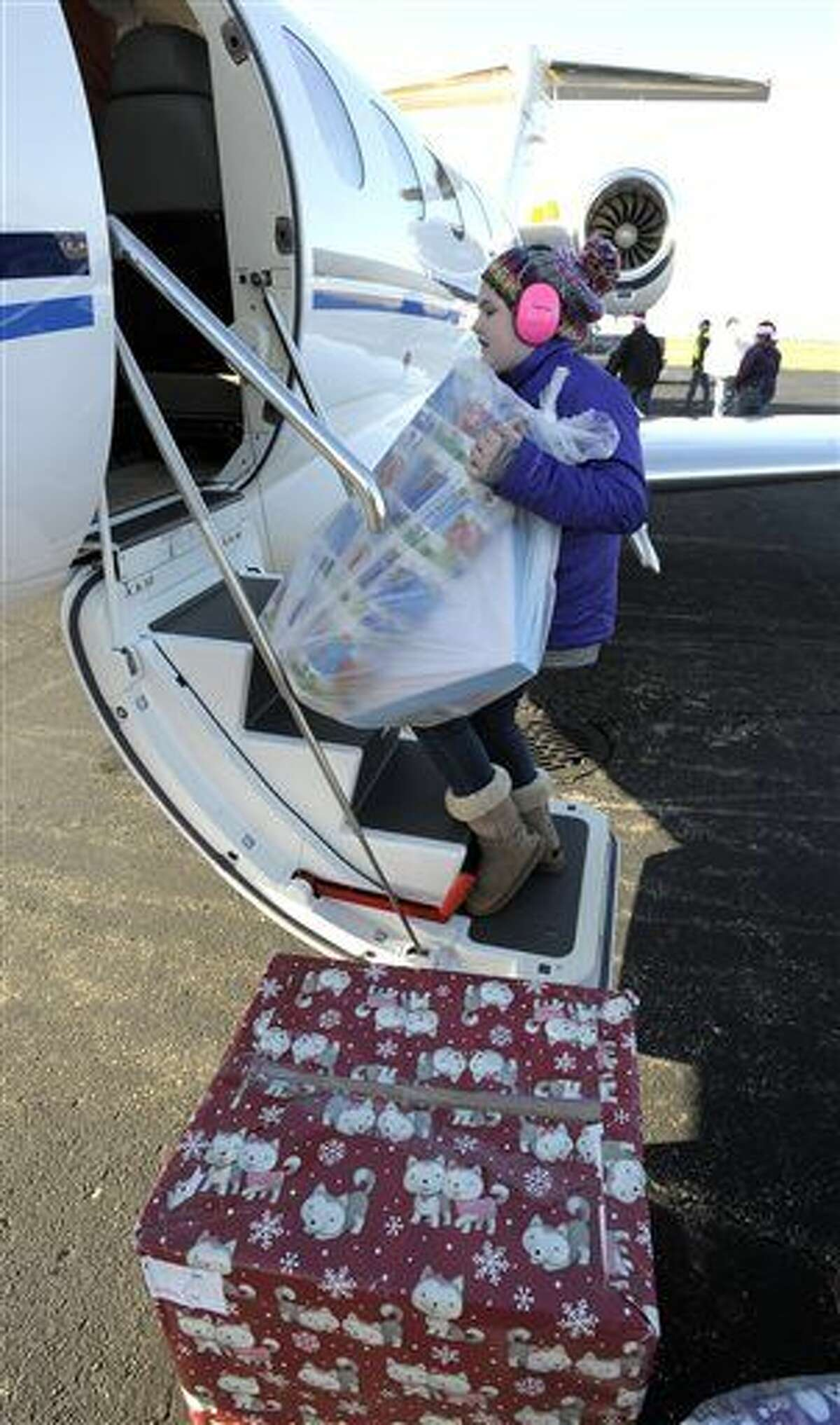 Kirsten Reid, 10, of Clarkston, helps load gifts into a jet as volunteers donate their time to deliver holiday gifts to thousands of children across Michigan during Operation Good Cheer at the Oakland County International Airport in Waterford Twp., Mich., Saturday, Dec. 5, 2015. (Todd McInturf/Detroit News via AP)