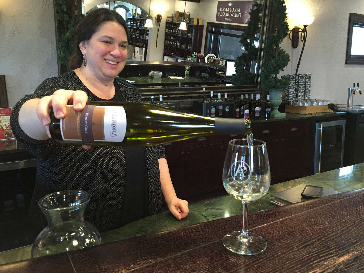 Dawn Bardenhagen pours a sample of wine in the tasting room at Aurora Cellars in Lake Leelanau. Aurora is part of the Northern Loop of the Leelenau Peninsula Wine Trail and offers a relaxed, informative tasting experience.