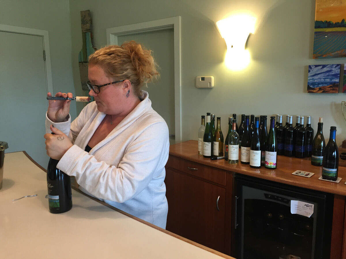 """Cortney Thibo, Bel Lago tasting room manager and event coordinator, inspects the cork from a freshly opened bottle of wine. """"We don't want them to just come in and taste,"""" Thibo said. """"We want them to ask questions."""""""