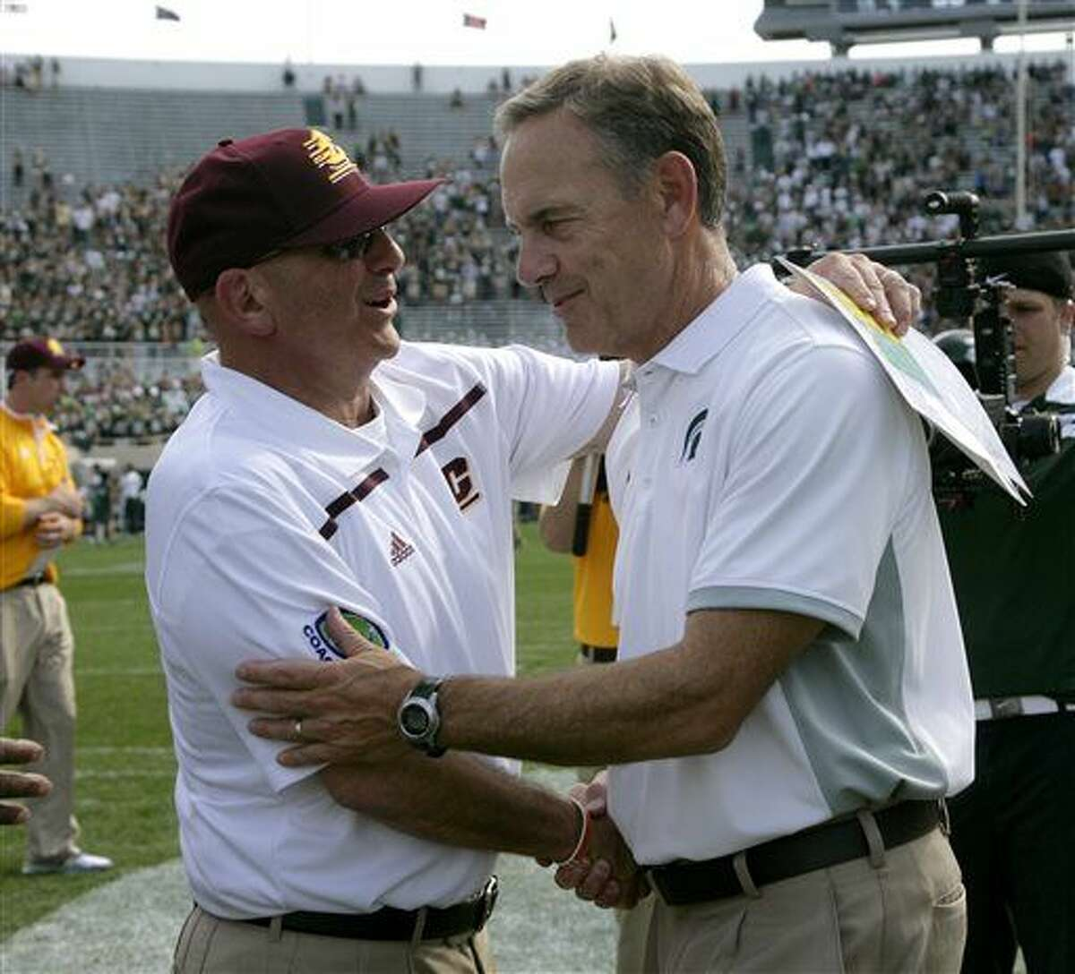 FILE - In this Sept. 26, 2015, file photo, Michigan State coach Mark Dantonio, right, and Central Michigan coach John Bonamego shake hands following an NCAA college football game in East Lansing, Mich. Central Michigan will play in the Quick Lane Bowl against Minnesota on Monday, Dec. 28, in Detroit. (AP Photo/Al Goldis, File)