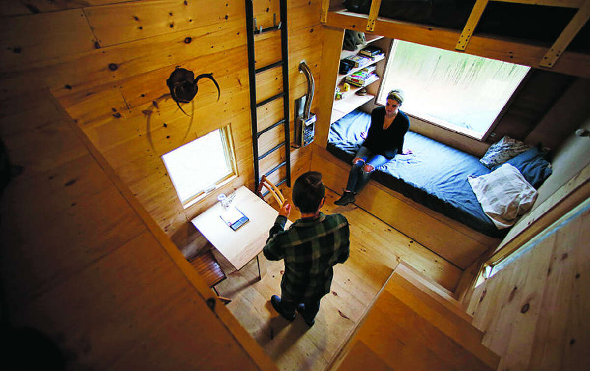 """In this Tuesday, Oct. 20, 2015 photo, Shane Lentz, of Pittsburgh, Pa., and his wife Hilary, talk before leaving a tiny house, which they rented for a weekend, in Croydon, N.H. As the tiny house phenomenon sweeps the nation, Harvard's Millennial Housing Lab thinks a tryout is in order for people toying with radically downsizing their lives. Its new """"Getaway"""" project gives the curious an opportunity to spend a night or two in one of three tiny houses and get a real feel for the lifestyle before taking the plunge. (AP Photo/Charles Krupa)"""