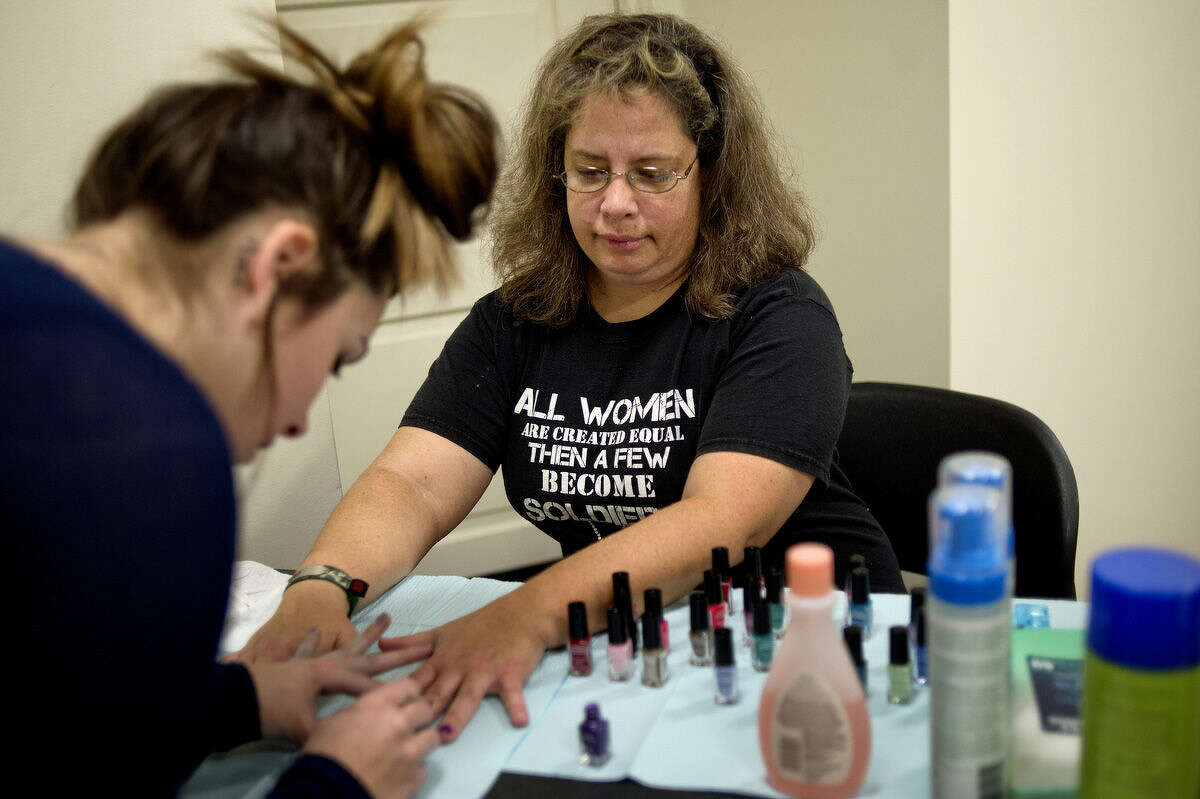 Veteran Sandra St. Onge, right, gets her nails done by cosmetologist Amanda Green during the Celebration of Sisterhood at the Aleda E. Lutz Veterans Affairs Medical Center in Saginaw. Volunteers gave manicures, pedicures and haircuts to veteran guests.