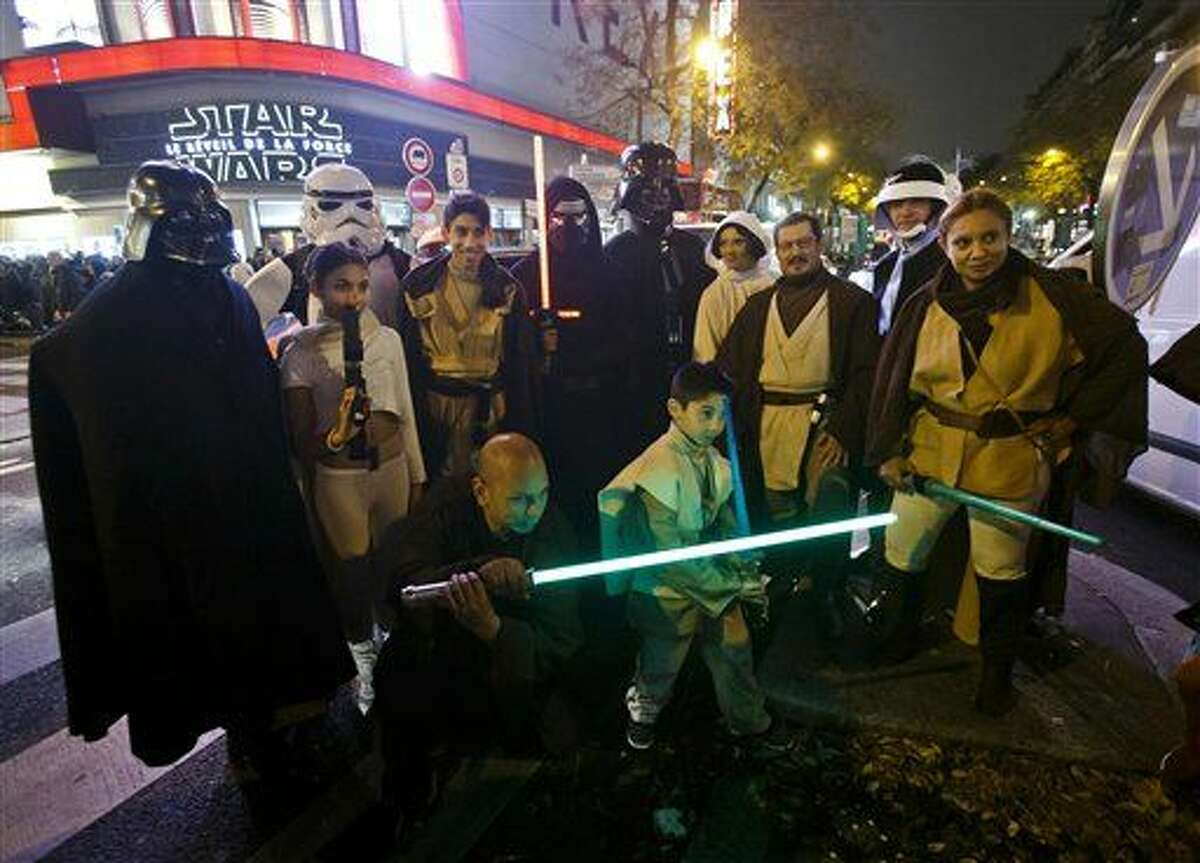"""Fans dressed in character wait outside of a movie theater prior to a screening of """"Star Wars: The Force Awakens""""in Paris."""