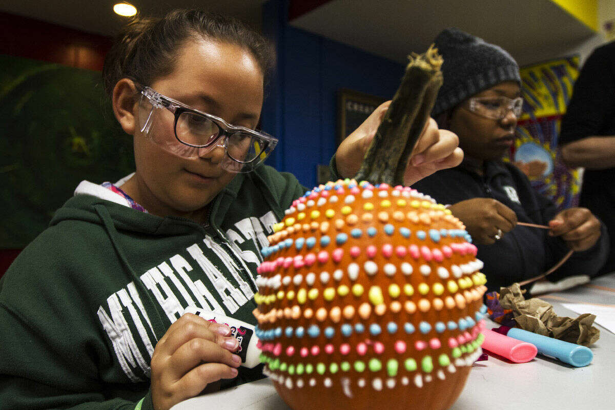 Kiana Prany, sixth-grader at Northeast Middle School, decorates a pumpkin using glow in the dark glue while participating in the Scientific Wonders and Artful Genius (SWAAG) program at Creative 360.