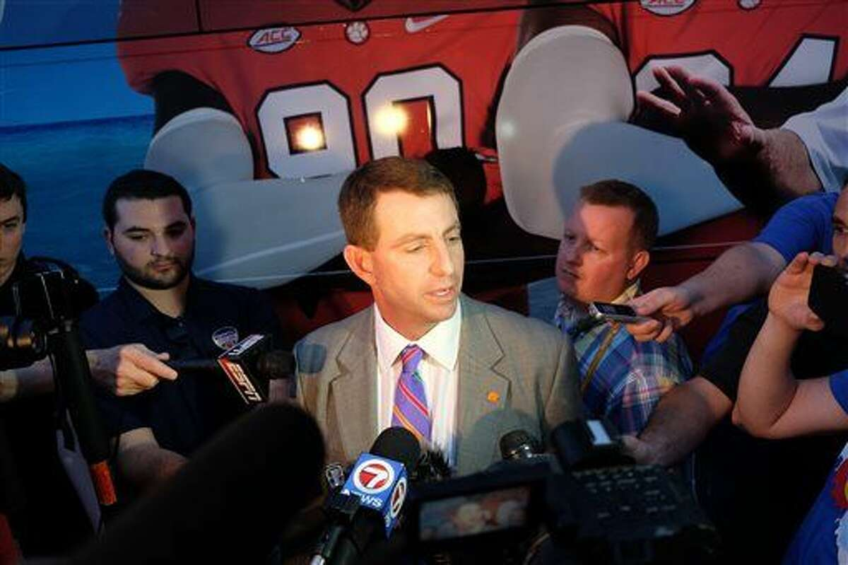 Clemson coach Dabo Swinney speaks with reporters after the team arrived in Fort Lauderdale, Fla., Saturday, Dec. 26, 2015. Clemson plays Oklahoma in the Orange Bowl NCAA college playoff semifinal Dec. 31 in Miami. .(AP Photo/Gaston De Cardenas)