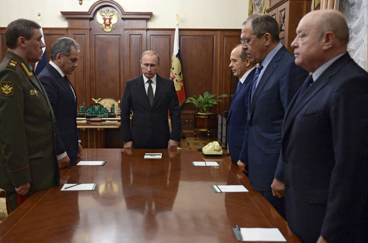 Russian President Vladimir Putin, third left, observes a minute of silence with Russia's Federal Security Service (FSB) head Alexander Bortnikov, third right, Russian Foreign Minister Sergey Lavrov, second right, and others before a meeting on Russian plane crash in Egypt, at Kremlin in Moscow, Russia, early Tuesday, Nov. 17, 2015. Bortnikov says the crash of the passenger plane in Egypt was the result of a 'terrorist' act. Bortnikov told Putin on Tuesday that a homemade explosive device blew up on the plane. Others are, the chief of General Staff, Gen. Valery Gerasimov, left, Defense Minister Sergei Shoigu, second left, and Foreign Intelligence Service head Mikhail Fradkov, right. (Alexei Nikolsky/SPUTNIK, Kremlin Pool Photo via AP)