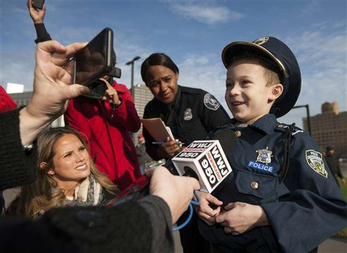 """Detroit Police """"Chief for a Day"""" Carter Widmer, 7, answers questions from the media after arriving at police headquarters in a helicopter on Wednesday, Dec. 23, 2015, in Detroit. Carter Widmer donated $250 of his Christmas money to the Detroit Police K-9 Unit. (John T. Greilick/Detroit News via AP)"""