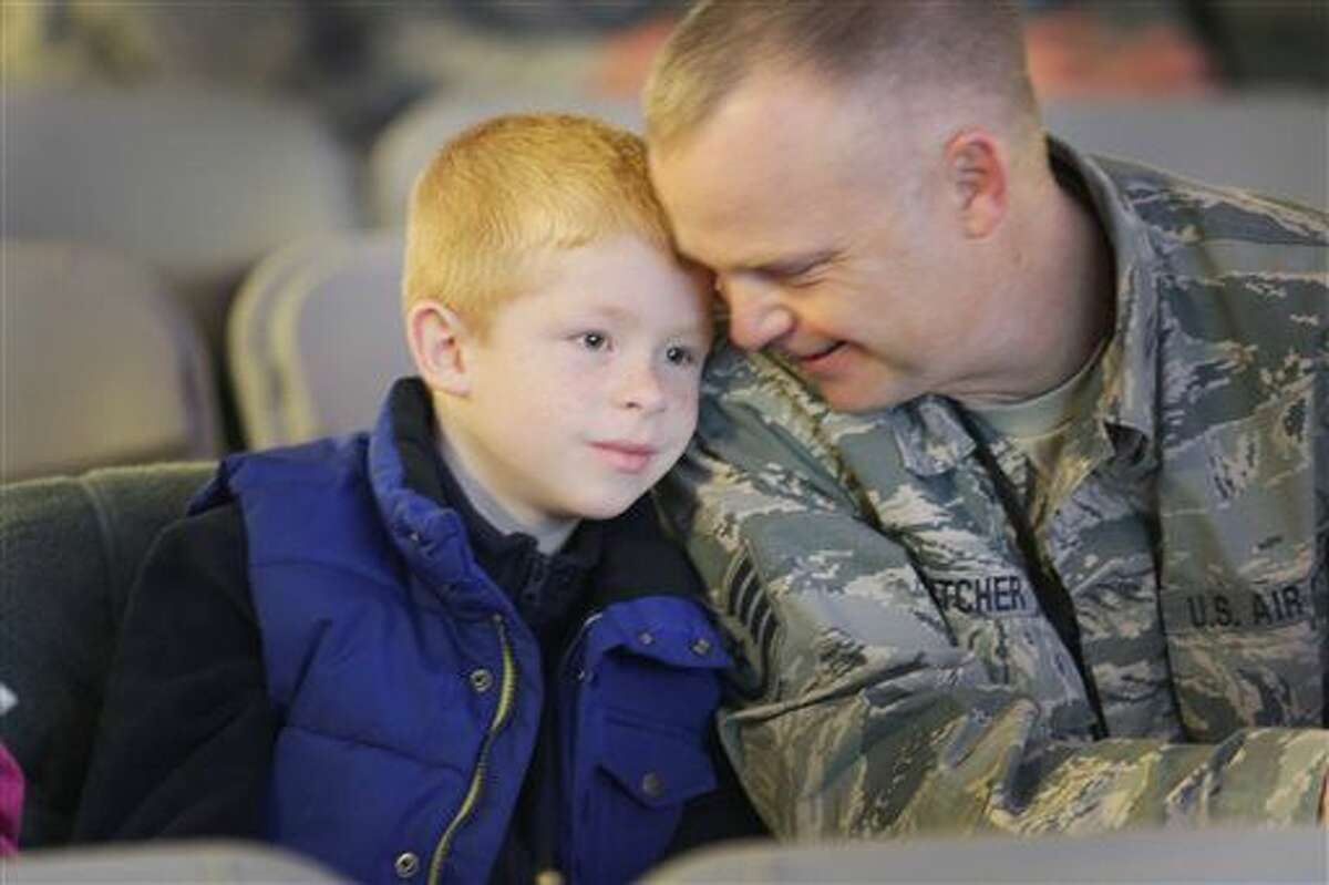 Joshua Wilhoit, 8, left , and his dad, Joe Wilhoit , a structural mechanic, with the 127th Wing share a moment together during the Welcome Home ceremony at Selfridge Air National Guard Base in Harrison Township, Sunday, Dec. 6, 2015. (Regina H. Boone/Detroit Free Press via AP)