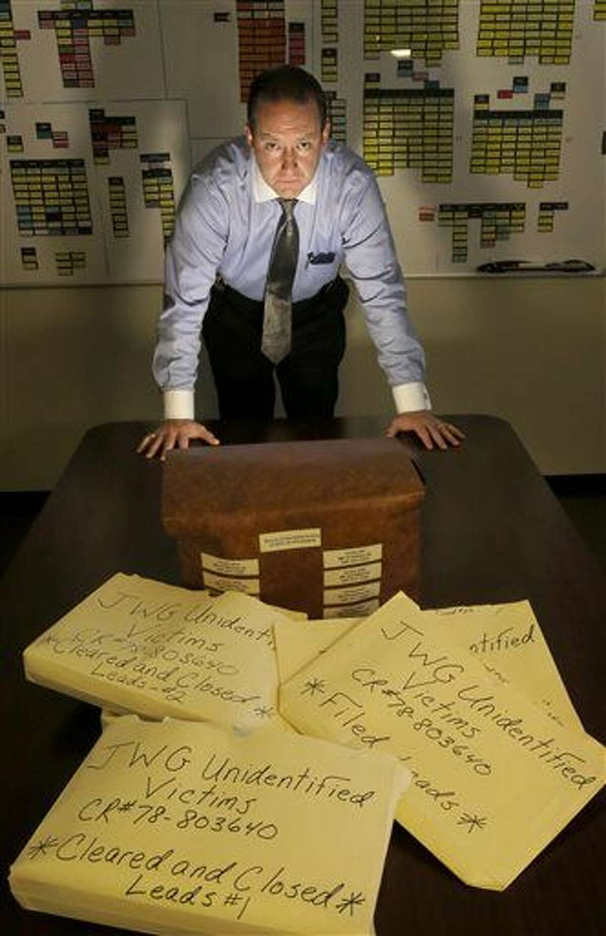 In this Thursday, Dec. 3, 2015 photo, Cook County Sheriff's Detective Jason Moran poses for a portrait with his case files of unidentified victims of serial killer John Wayne Gacy in Maywood, Ill. While working to identify these victims, Moran has cleared 11 cold cases across America that had nothing to do with Gacy. (AP Photo/Charles Rex Arbogast)