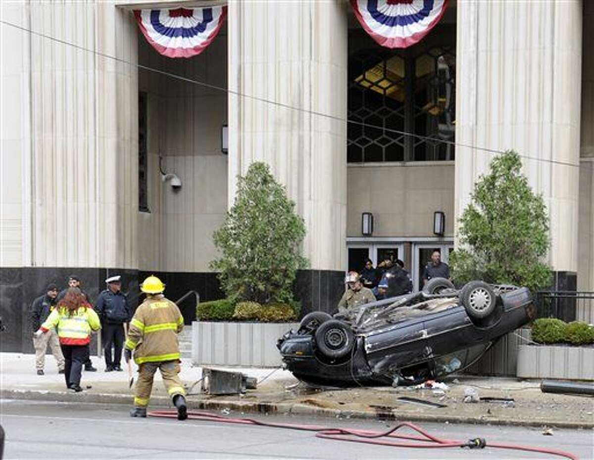 Rescue personnel appear at the scene of a car crash outside of the Theodore Levin U.S. Courthouse, Tuesday, Nov. 24, 2015, in downtown Detroit. The vehicle had flipped over early Tuesday, leaving the driver trapped inside. (Chris Farina/The Detroit News via AP)