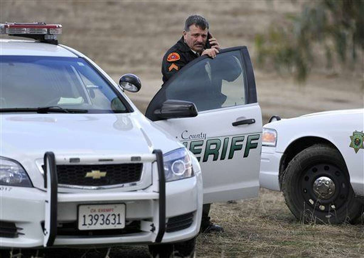 A Kern County Sheriff Deputy listens to a police radio at the command center several miles from the site of a helicopter crash Friday near McFarland, Calif. A medical helicopter carrying a patient to a hospital crashed in heavy rain and fog in California's agricultural San Joaquin Valley, killing all four people aboard, officials said.