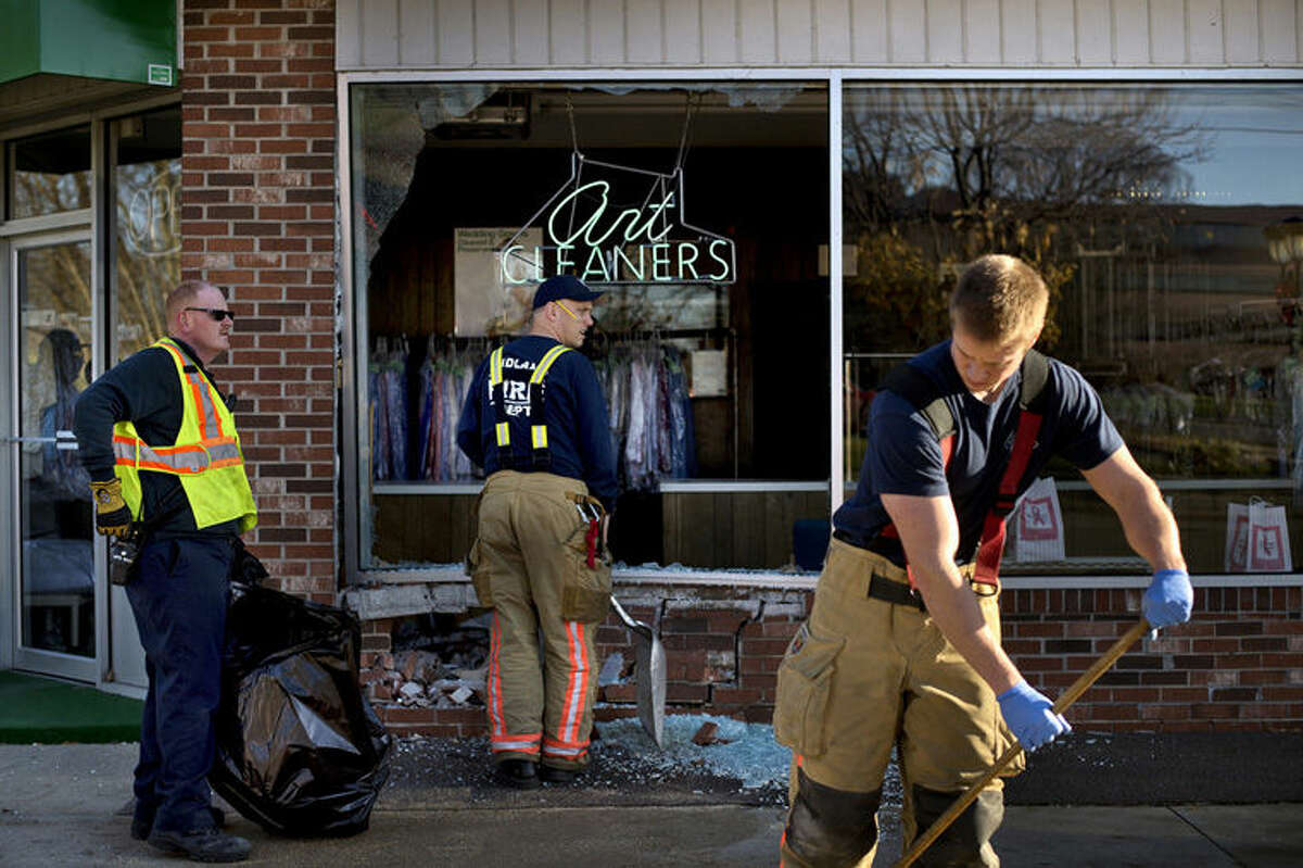 Midland firefighters clean up after one of the vehicles involved in a two-car crash rammed into Art Cleaners at the corner of Buttles and Ashman streets on Sunday afternoon in Midland.