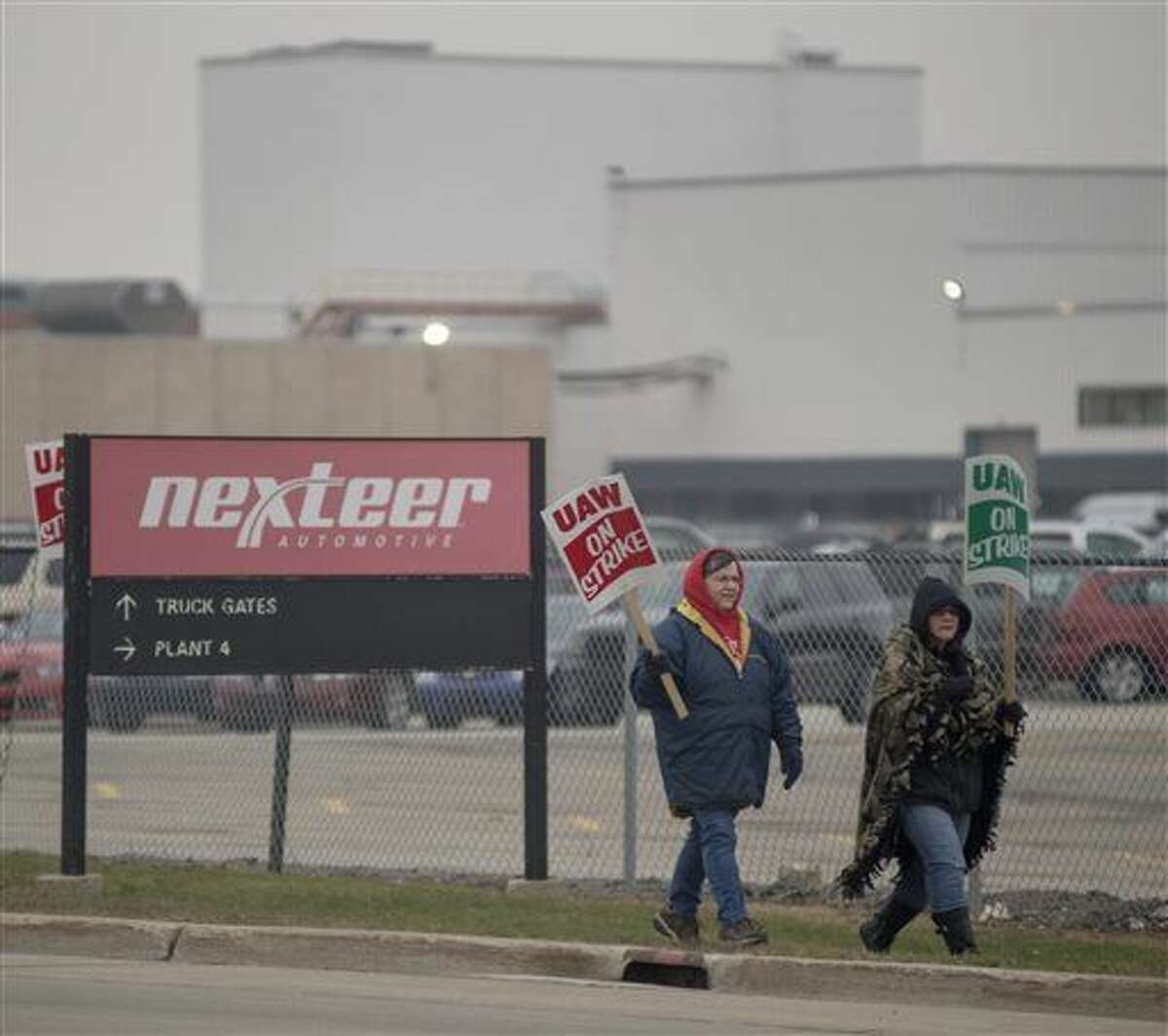Members of UAW Local 699 hold signs as they picket outside of the Nexteer Automotive plant in Saginaw County's Buena Vista Township, Mich., Tuesday, Dec. 8, 2015. United Auto Workers union members at a Nexteer Automotive manufacturing complex in Michigan walked off the job after workers rejected a tentative contract with the auto parts supplier. (Jeff Schrier/The Saginaw News/MLive.com via AP)