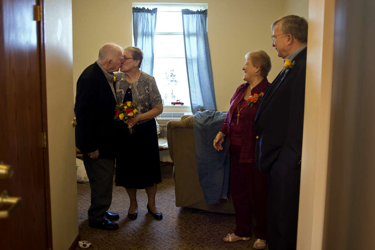 """BRITTNEY LOHMILLER   blohmiller@mdn.net Jack Moore, left, kisses his wife Katherine Moore before walking to their vow renewal ceremony on their 43rd wedding anniversary at Bickford Senior Living Wednesday afternoon. Jack's younger sister Sue Hanson, right, and her husband Jerry Hanson attended the ceremony. """"We never had fight,"""" Katherine said. """"We had a few mild disagreements but never a fight."""""""