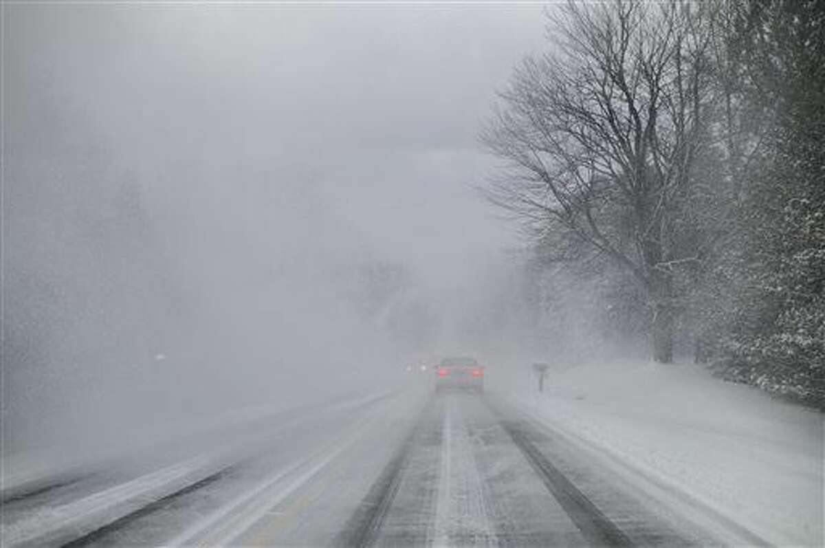 A car navigates near white-out conditions on Pine Island Drive as people try to find alternate routes to US-131 after a pileup there on Friday, Dec. 18, 2015. Slick road conditions were blamed on lake effect snow. (Neil Blake/Grand Rapids Press-MLive.com via AP)